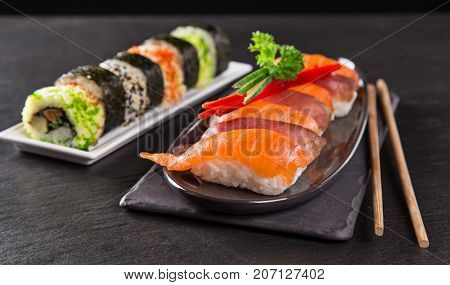 Japanese sushi set on a rustic dark background, close-up.