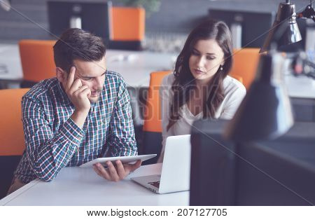 Two colleagues working together on an innovative product design in a creative studio. Young Casual business couple using computer in the office. Coworking, Creative manager showing new startup idea