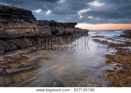 Howick Coastline Rocks, on the shoreline at Howick on the Northumberland coasts AONB, showing motion blur of the North Sea