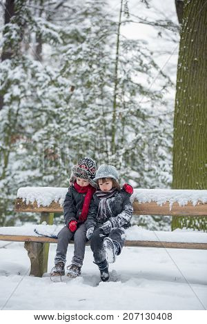 Two Children, Boy Brothers, Sitting On A Bench In Park, Wintertime While Snowing