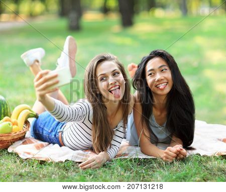 Caucasian And Asian Young Woman Doing Selfie And Showing Tongues