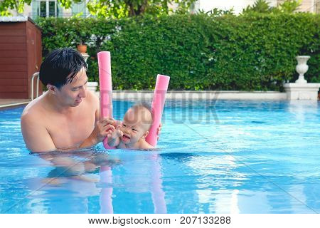 Cute little Asian 18 months / 1 year old toddler baby boy child learning to swim with pool noodle with dad at outdoor pool dad and son relaxing in swimming pool of clubhouse in sunny summer day with copy space