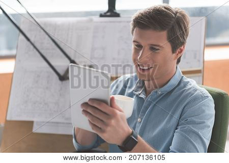 Joyful mood. Cheerful young architect is drinking coffee and looking at screen of modern tablet while resting in office. Drawing board with blueprint in background