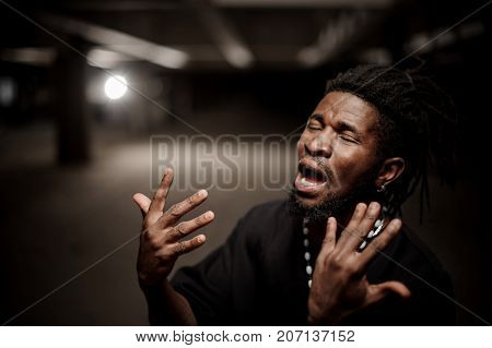 Emotional close up portrait of the young gesticulating afro american guy in black T-shirt on the dark background