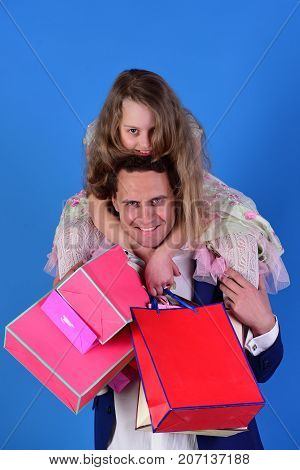 Schoolgirl sits on dads shoulders. Girl and man with happy smiling faces hold shopping bags on blue background. Daughter and dad with pink and red packages. Shopaholics childhood and family concept