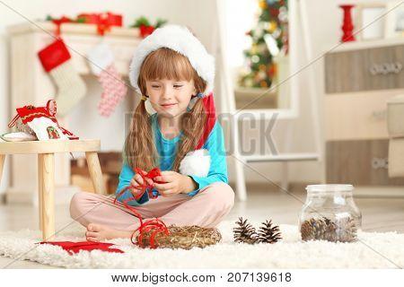 Cute girl decorating Christmas wreath on floor