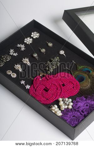 Women's Earrings And Rings In A Special Box For Storage. A Collection Of Jewelry For Different Occas