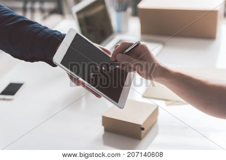 Put it here. Close-up of digital tablet in hand of courier and stylus in hand of young guy. Employee is appending his signature after accepting delivery of box. Workplace in background