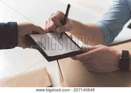 Confirmation. Close-up top view of hand of professional courier is holding folder while recipient male is signing invoice and accepting delivery of box