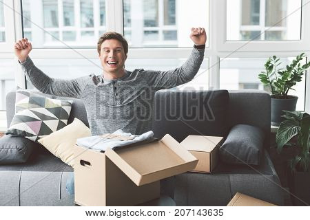 Portrait of cheerful young man flourishing arm near open post box with goods. He locating at home