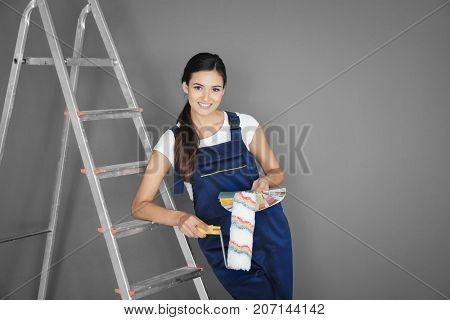 Young female decorator with paint roller and color palette samples near ladder against grey background
