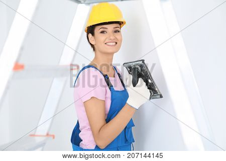 Young female decorator working with plastering trowel indoors