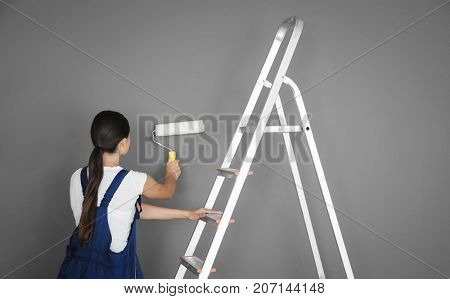 Young female decorator painting wall in room
