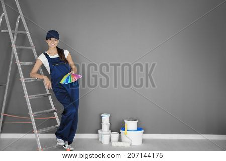 Young female decorator with color palette samples near ladder in room
