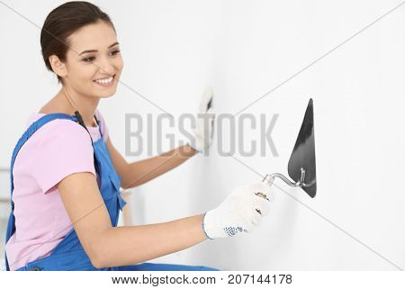 Young female decorator working with trowel indoors