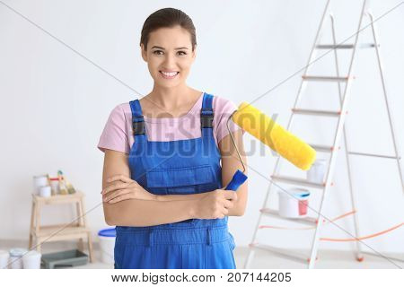 Young female decorator with paint roller in room