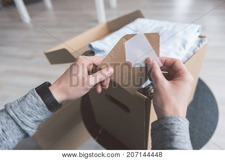 Close up man arms keeping letter opposite package. He situating in room. Delivery concept