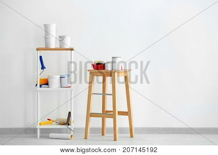 Composition with paint and decorator's tools near white wall