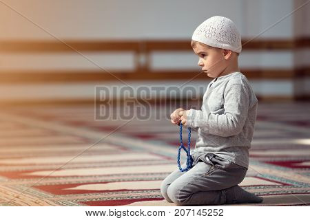 Ramadan Kareem, The Muslim boy prays in the mosque, the little boy prays to God, Peace and love in the holy month of Ramadan, lifestyle concept