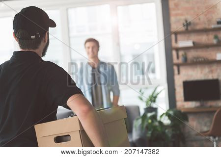 Bearded young courier keeping package in hand. He bringing it to smiling young client while turning back to camera. Copy space