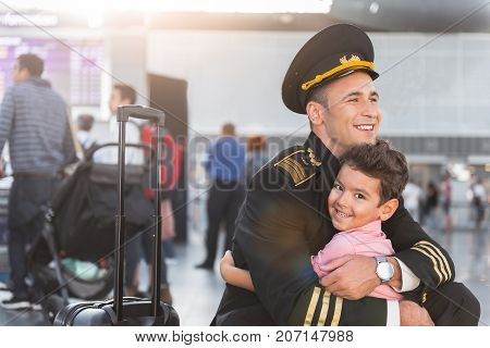Happiest moment. Cheerful little boy is meeting father, who working as pilot. Portrait. Copy space on left side