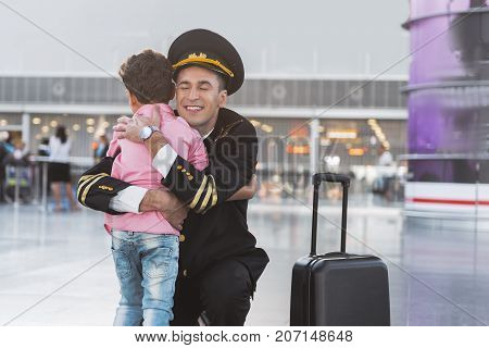 Family reunification. Joyous pilot is squatting and hugging little son in airport. Portrait. Copy space on right side