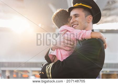 Happy male pilot is hugging his child after long separation. Waist up portrait. Copy space on left side