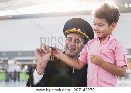 Your father flying at such plane. Cheerful pilot is squatting near son and they holding toy aircraft. Portrait. Copy space on left side