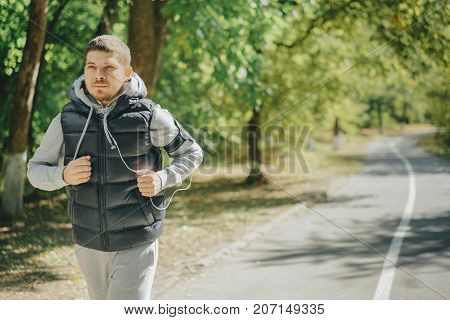 young active male runner in a tracksuit and jumper with headphones. Training for health in the park in the fall.