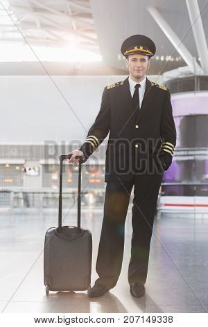 Cheerful male pilot is looking at camera with smile. He holding his luggage. Full length portrait. Copy space on left side