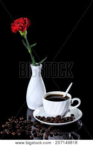 Composition Of Coffee And Red Carnation On A Black Reflective Background