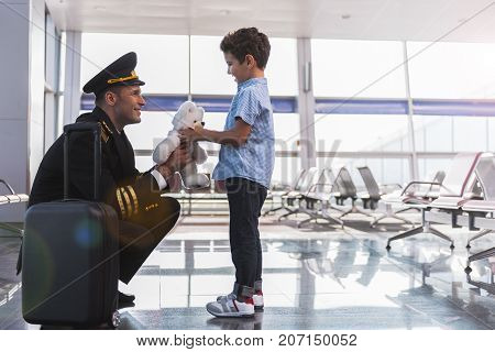 Cheerful pilot is giving son little teddy bear and looking at him with sincere smile. They locating in airport. Profile. Copy space on right side