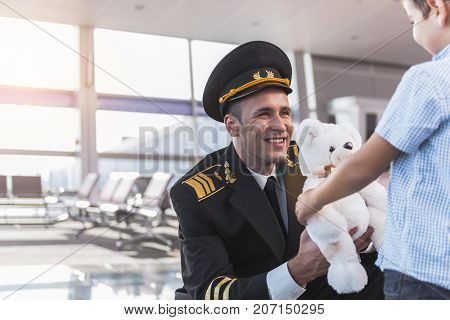 Hilarious pilot is presenting white teddy bear to son and looking at child with happy smile. Portrait. Copy space on left side