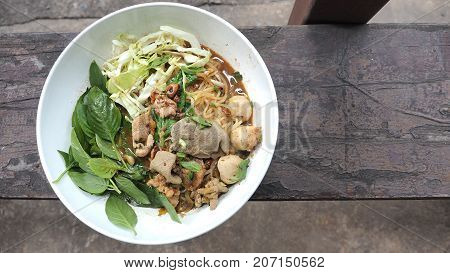 Boat noodles pork Thai food classic and popular menu and ready to eat in white bowl on vintage wood at shop photo top view has cop space.