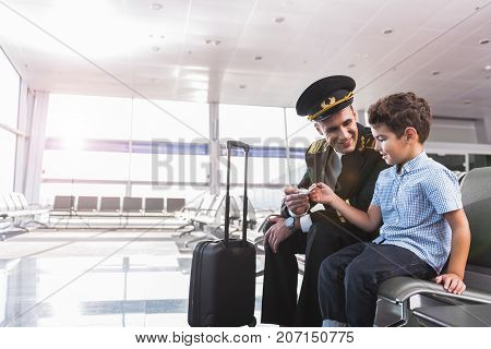 Happy dad pilot is sitting beside his child in waiting hall. They holding small toy plane. Portrait. Copy space on left side