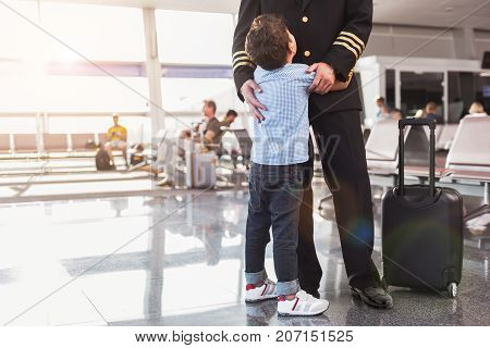 Little son is embracing pilot. They standing in waiting hall of airport. Focus on kid back. Copy space on left side
