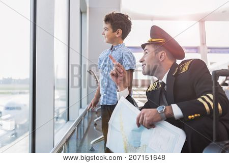 Glad father aviator is squatting near interested son and pointing up. Kid looking through glass wall with smile. Copy space on left side