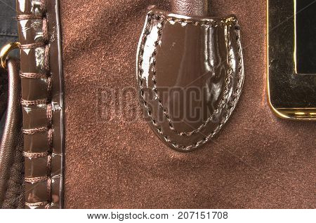 closeup of buckles, clasps, zippers, pockets, fasteners, fittings and seams on brown leather hand bag