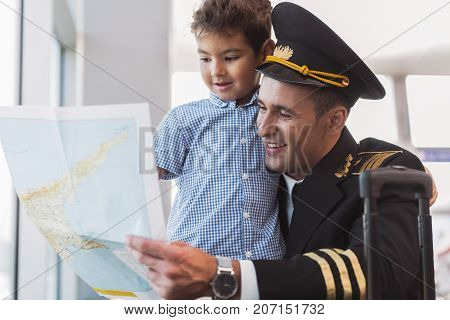 Joyous dad pilot is squatting near child and showing him unfolded map. They locating nearby window. Portrait. Low angle