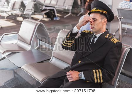Tired pilot is sitting on bench in waiting hall of airport. He closing eyes. Portrait. Copy space on left side