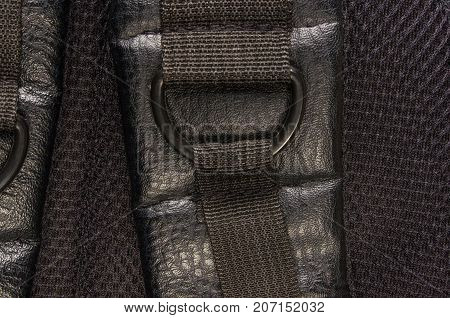 closeup of buckles, clasps, zippers, pockets, fasteners, fittings and seams on black leather backpack