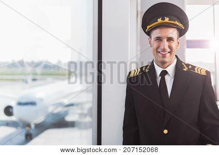 Glad aviator wearing uniform and looking at camera with bright smile. He standing near glass wall. Waist-up portrait. Copy space on left side