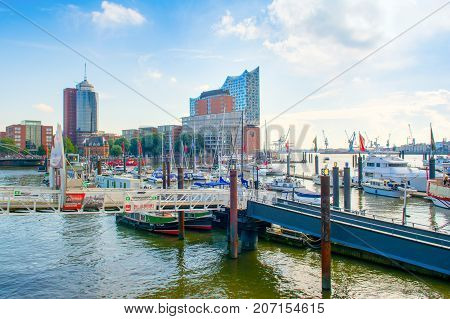 Hamburg Germany - 17 September 2017: Sailing yachts powerboats ships and other water transport in the port of Hamburg. Modern building of Elbphilharmonie on background.