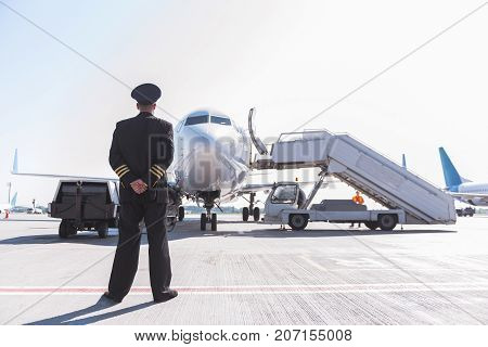 Pilot wearing uniform is standing outside and looking at tremendous plane. He turning back to camera. Copy space