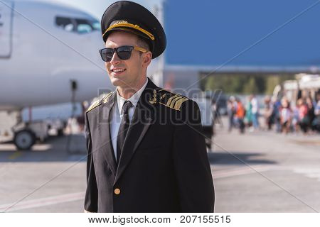 Pride of aviation. Joyous pilot is standing outside and looking ahead with smile. He wearing sunglasses. Waist up portrait