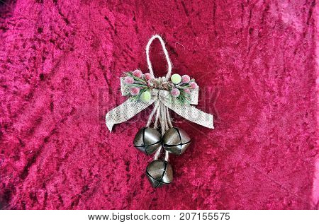 Christmas Sleigh Bells Tied To A Bow On A Red Background