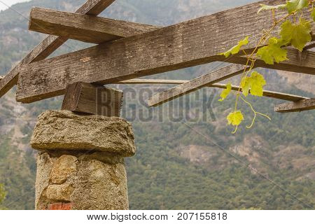 detail of a pylon in stone and lime of the vineyards  of Carema,Piedmont,Italy / a pylon stone and lime with the span on which the pergola of vineyards is supported