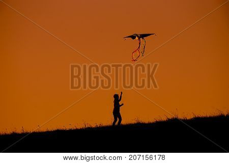 Silhouette Of Woman Flying A Kite Top Of Mountain Sunset Evoke Emotion Happy Memories.  Doi Mon Jong