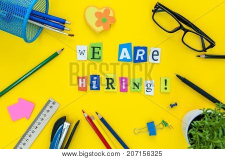WE ARE HIRING CONCEPT ON yellow work place, office background with supplies.