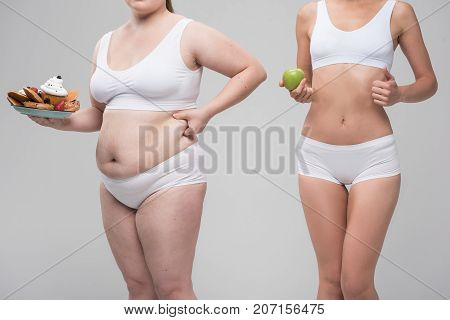 You are what you eat. Close up of body of slim girl holding an apple and giving thumb up. Fat one is carrying plate of sweet pasty and touching her large abdomen. Isolated